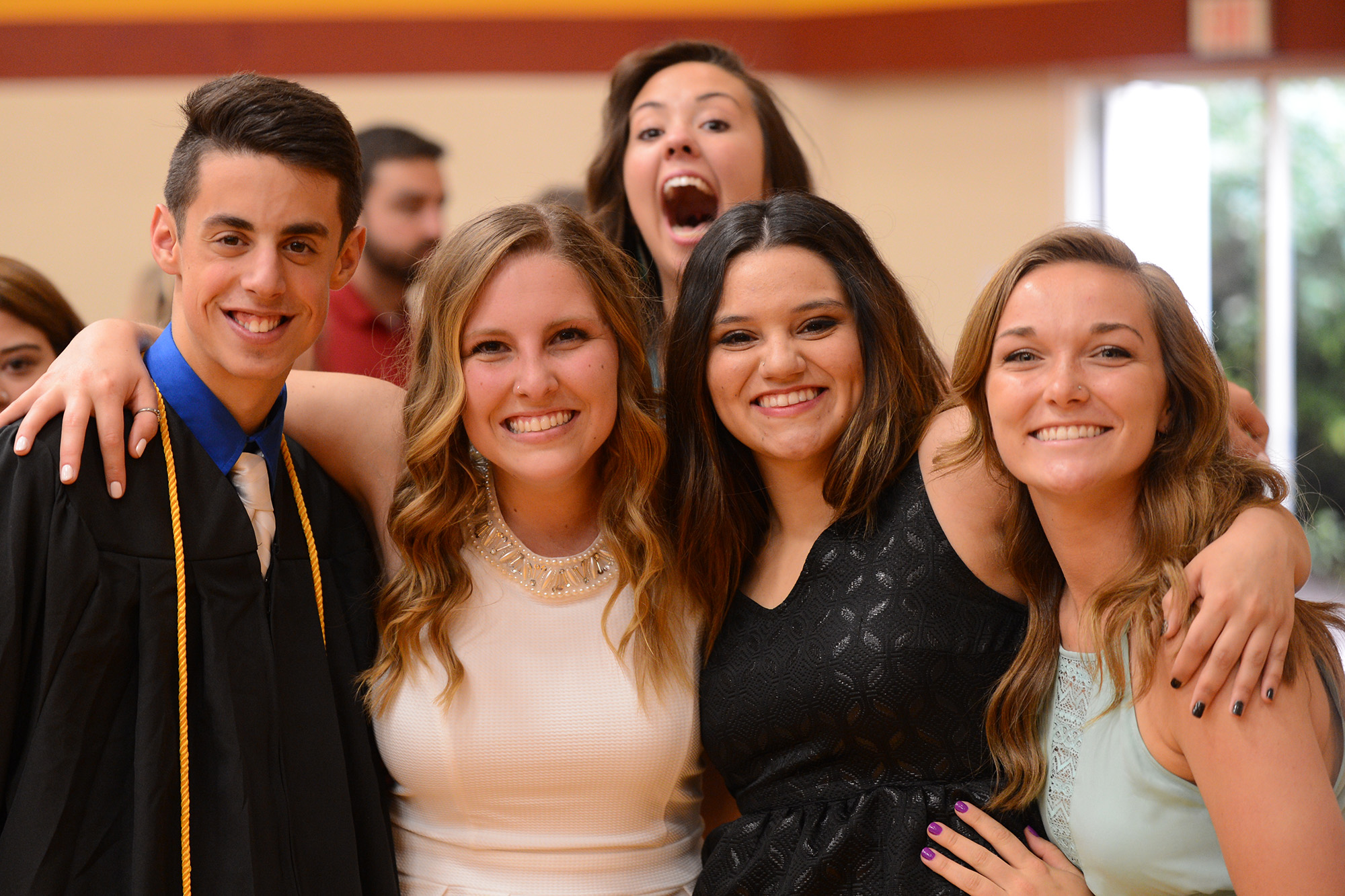 Graduates Bryce Nitzshe, Kiara Boettger, Casey Perez and Meredith Spicher take a final Hesston College photo together while Molly Bruner jumps in late.