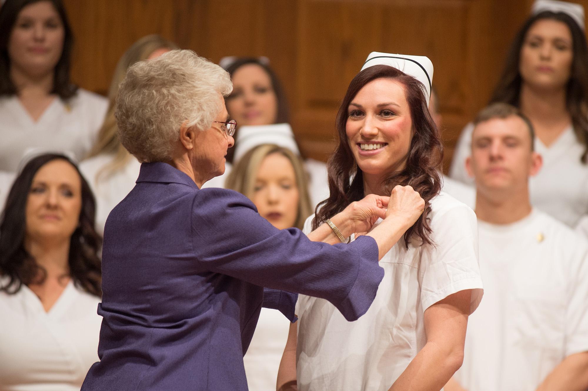 Maelyn Loch '16 (Wichita, Kan.) receives her nursing pin from instructor Joyce Huber during the 49th Nursing Pinning Ceremony.