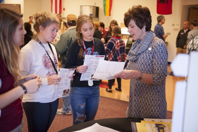 Deb Roth, Dean of Student Success (right), talks through a two-year plan of study with prospective students and admissions counselor Carley Wyse (left) during a Friday Experience Expo, highlighting academic and extracurricular opportunities at Hesston.