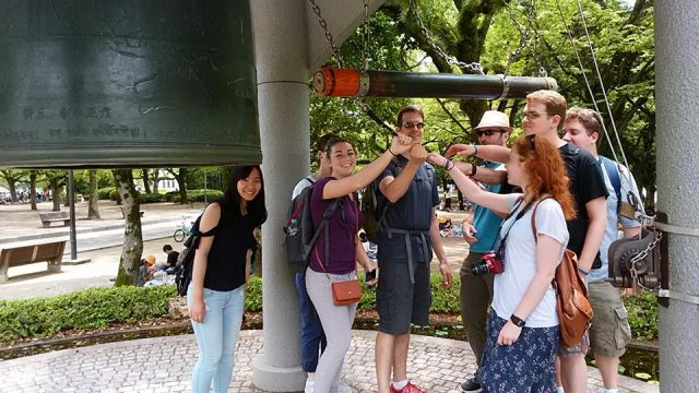 Participants on the May Term Japan trip ring the Hiroshima Peace Bell.