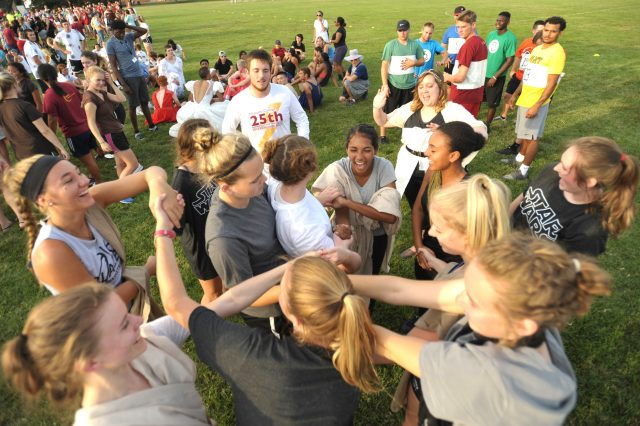 "A mod works to untangle themselves during the ""Human Knot"" game at Mod Olympics, the final kick-off event of Opening Weekend prior to the start of classes. Each mod's uniquely themed style of dress and the nonsensical games allow students to have fun and get to know one another in a laid back setting."