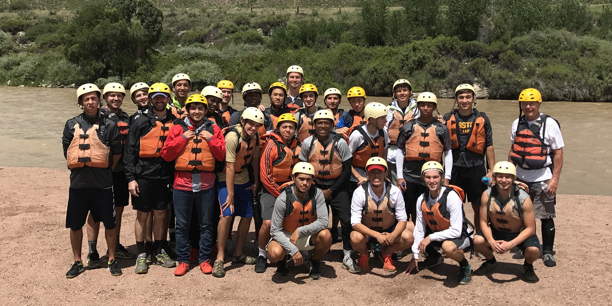 The team prepares to go whitewater rafting with former Hesston academic dean Marc Yoder (right).