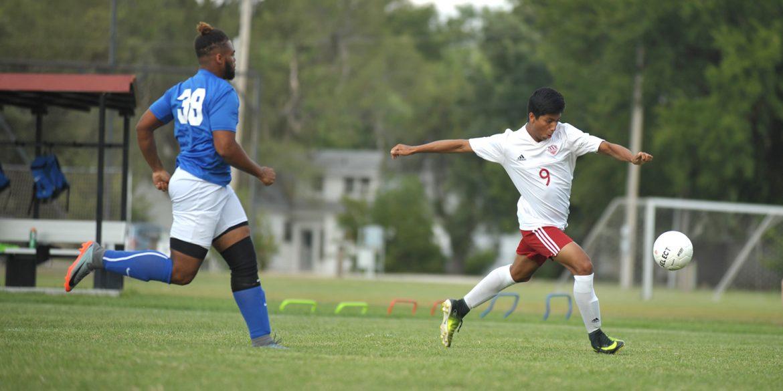 Hesston College men's soccer player Javier Reyna shoots in a 2017 season match.