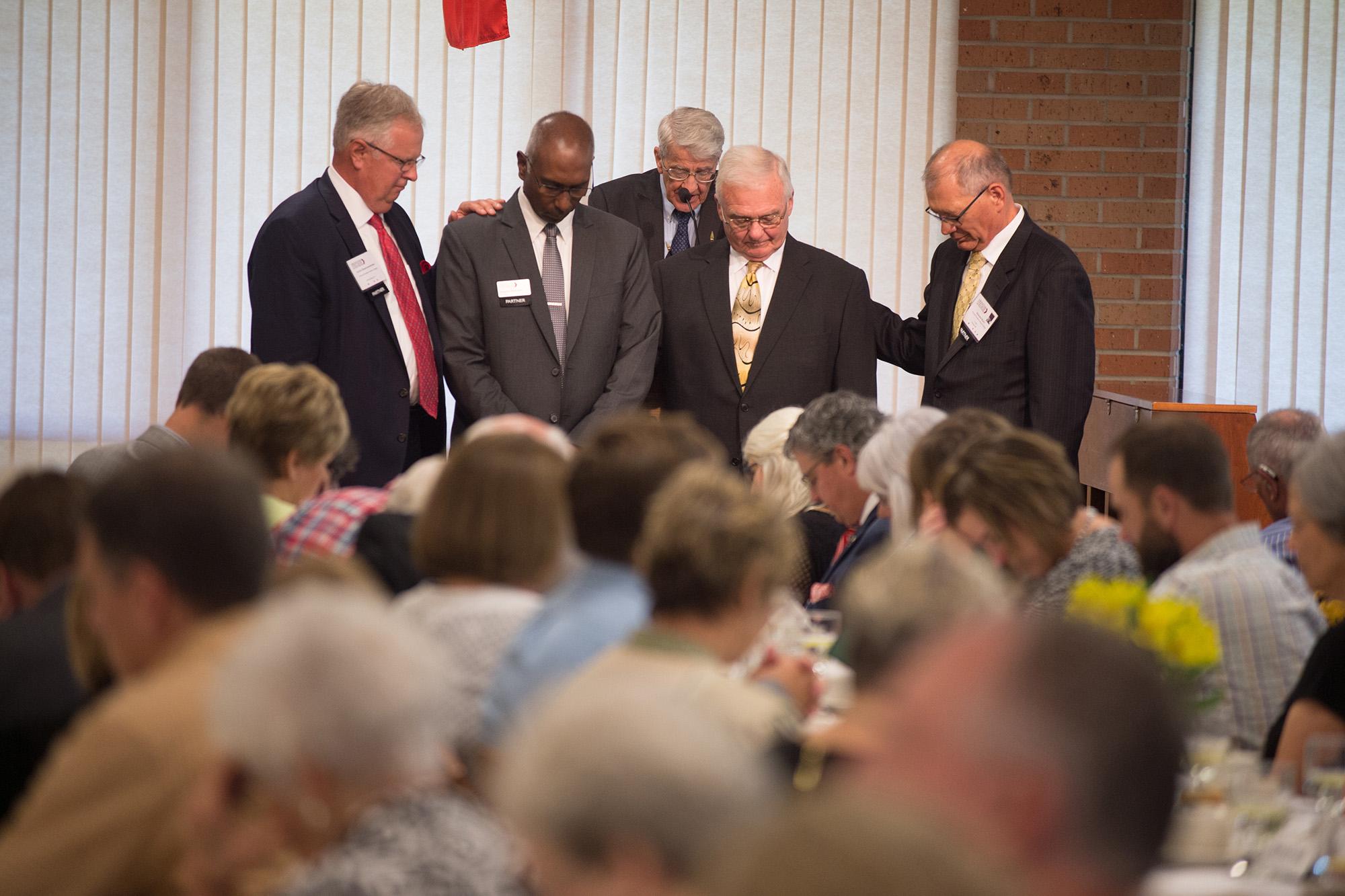 Hesston's four living former presidents pray a prayer of blessing for the college's ninth president. Dr. Joseph Manickam.