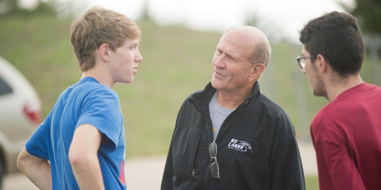 Coach Gerry Sieber visits with freshmen Brandon Kirby (Potwin, Kan.) and Tobias Belknap (Inman, Kan.) at practice.