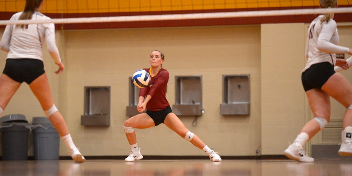 Hesston College volleyball action photo - Kylie Brenneman digs in a match with Cloud County CC, Oct. 6, 2017