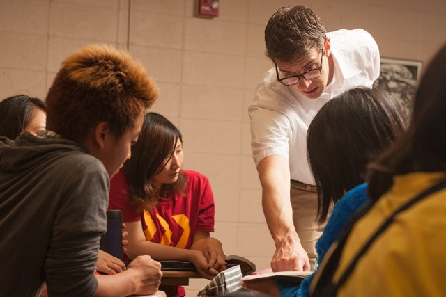English as a Second Language professor André Swartley '99 works with students in class.