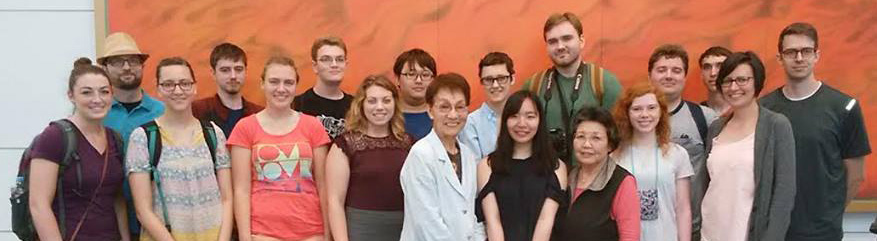 The May Term in Japan group take a photo with a survivor of the Hiroshima atomic bomb (center) after hearing her story.