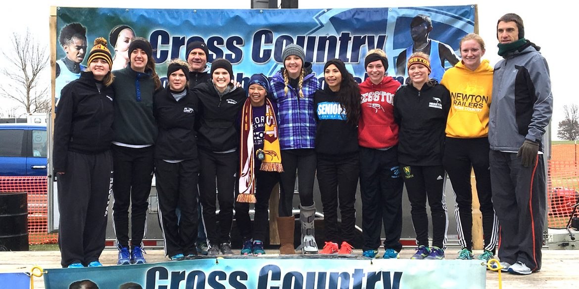 Hesston College's women's cross country team poses in front of a banner at the NJCAA national meet.