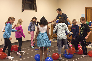 Sophomore Preston Judd organizes a group of children for a game at Whitestone Mennonite Church's WOW program.