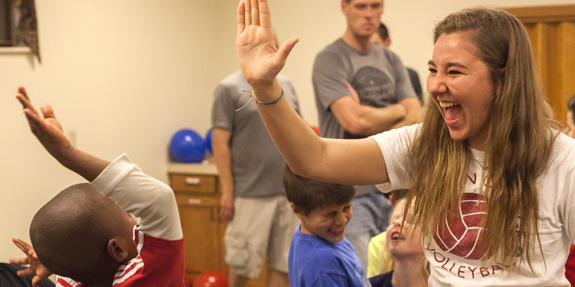 Freshman Cassidy King high fives a WOW participant during a game.