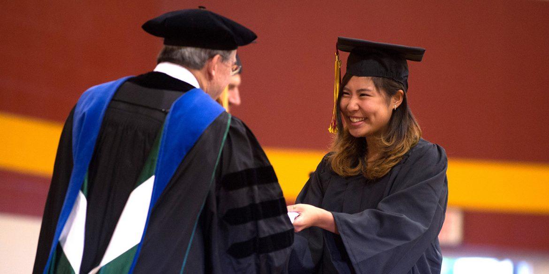 Mika Matsuda receives her diploma from interim President Ben Sprunger.