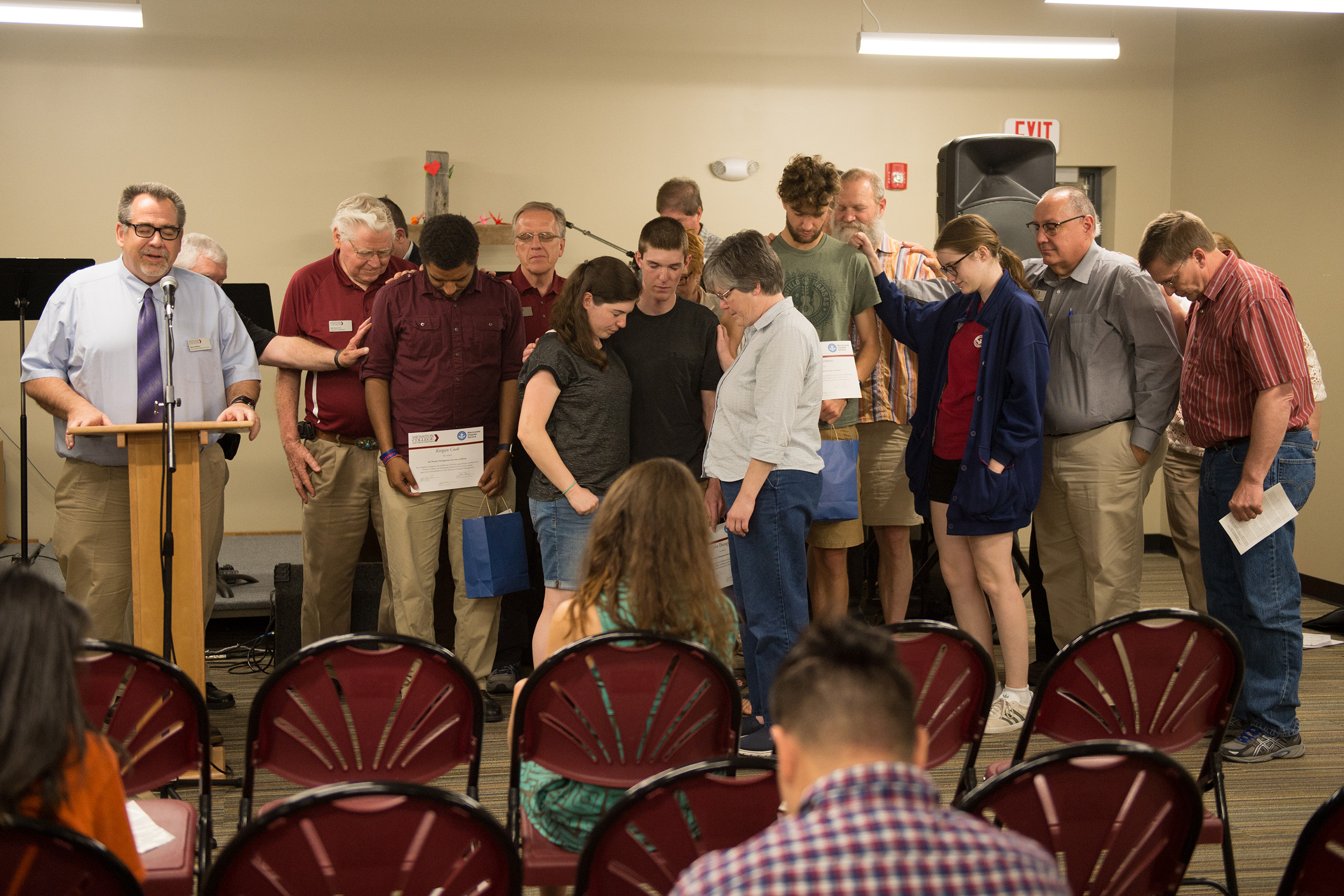 "Disaster Management graduates are surrounded for a commissioning at a recognition ceremony in their honor May 12. Krista Rittenhouse '12 delivered the ceremony message, ""It every day bro."" Rittenhouse serves with Mennonite Mission Network's Service Adventure in Johnstown, Pa."