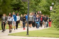 Students walk the avenue of flags.