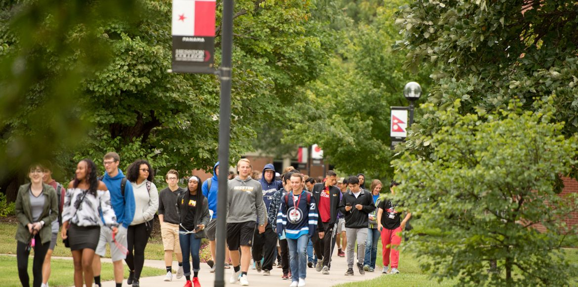 During Peace Day 2018, students walk the Hesston College Global Walkway, which is lined with flag representations of the countries Hesston College students call home.