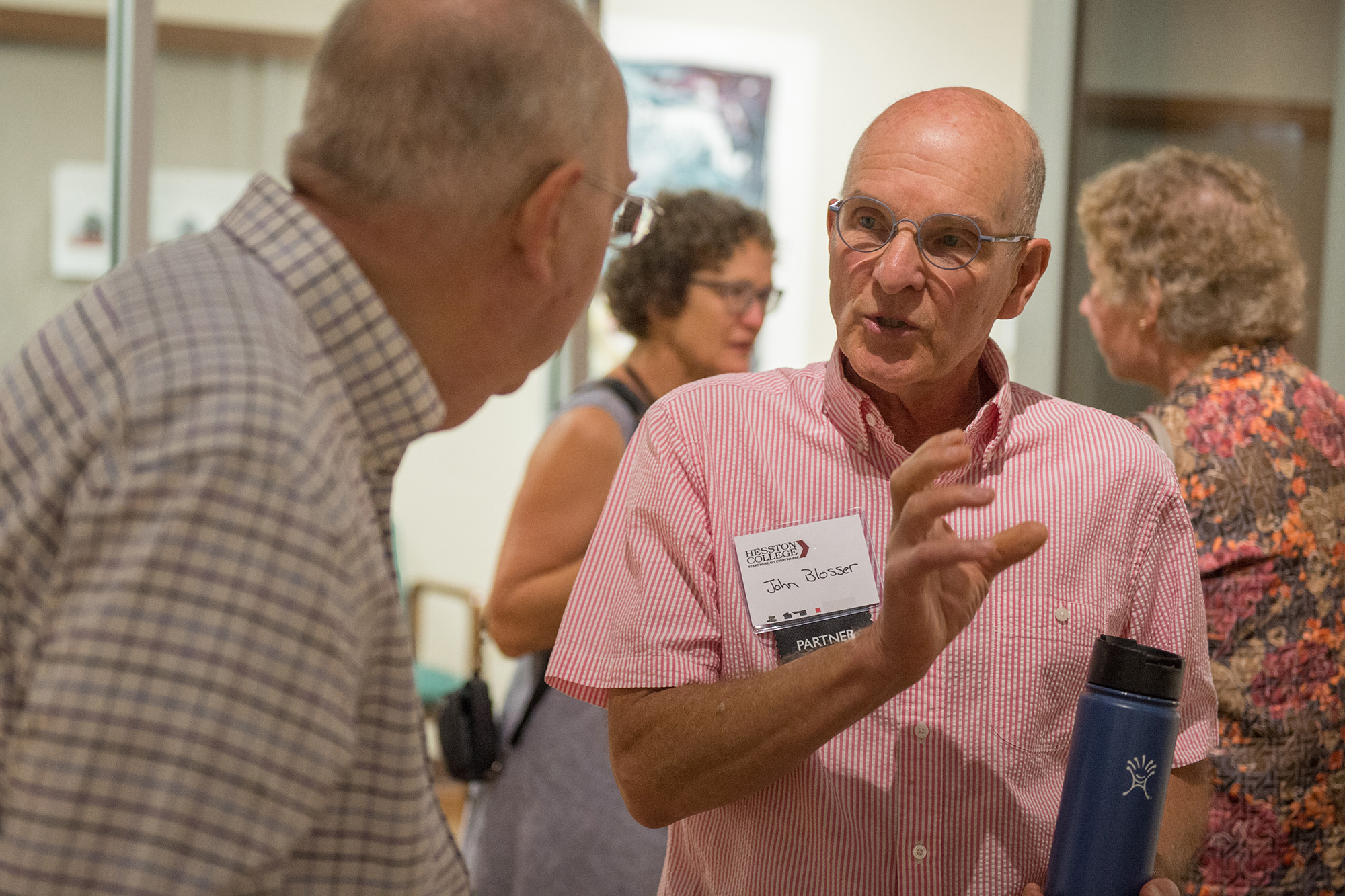 Former art prof John Blosser visits with former physics prof Nelson Kilmer at an artist's reception for Blosser's exhibit.