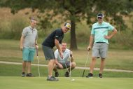 Ryan Roth lines up a putt at the Homecoming Golf Benefit in honor of Floyd Sowers '71 for his years of volunteer service in organizing and managing the benefit on behalf of the college. Watching in the background are Blake Buhrman '01, Tyson Miller and Steve Martin '04, Alumni Association President.