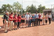 Chelsey Smith '20 (left center) joins Mick Mullet '76 and Dave Mullet Ac62, '64 and others in the ribbon cutting for the new on-campus Bess Mullet Softball Field. The five Mullet brothers have long been Hesston College donors and given to special projects, including the field, which is named in honor of their mother.