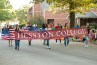 Students represent Hesston College in the community-wide Home Sweet Hesston Homecoming parade. Carrying the banner from left are Romina Xhari '21 (Lezhe, Albania), Unique Froese '20 (Ordway, Colo.), Olivia Hernandez '23 (Hesston) and Sidorella Mjeshtri '21 (Lac, Albania). Second row carrying flags from left: Brooke Brenneman '20 (Parnell, Iowa), Josh Wilson '21 (Canterbury, New Zealand), Kate-Lyn Tivert '21 (Kigali, Rwanda) and Evelyn Worku '20 (Addis Ababa, Ethiopia).
