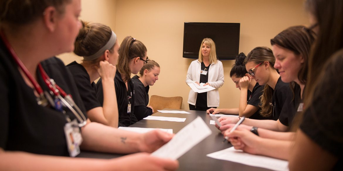 Students meet with faculty member Sharon Woodward to debrief after a clinical shift.