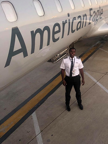 Ashenafi Tadese stands next to the American Eagle plane he flies