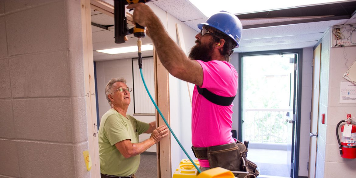 Mennonite Disaster Service volunteers Don Horst and Jordan Miller install a wall to add a room to a Kauffman Court mod.