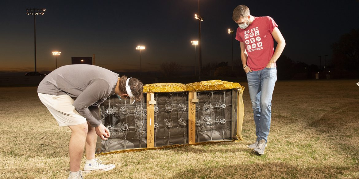 Jacob Mullins and Chris Lichti inspect Goldy's underside, where previous caretakers have written their names.